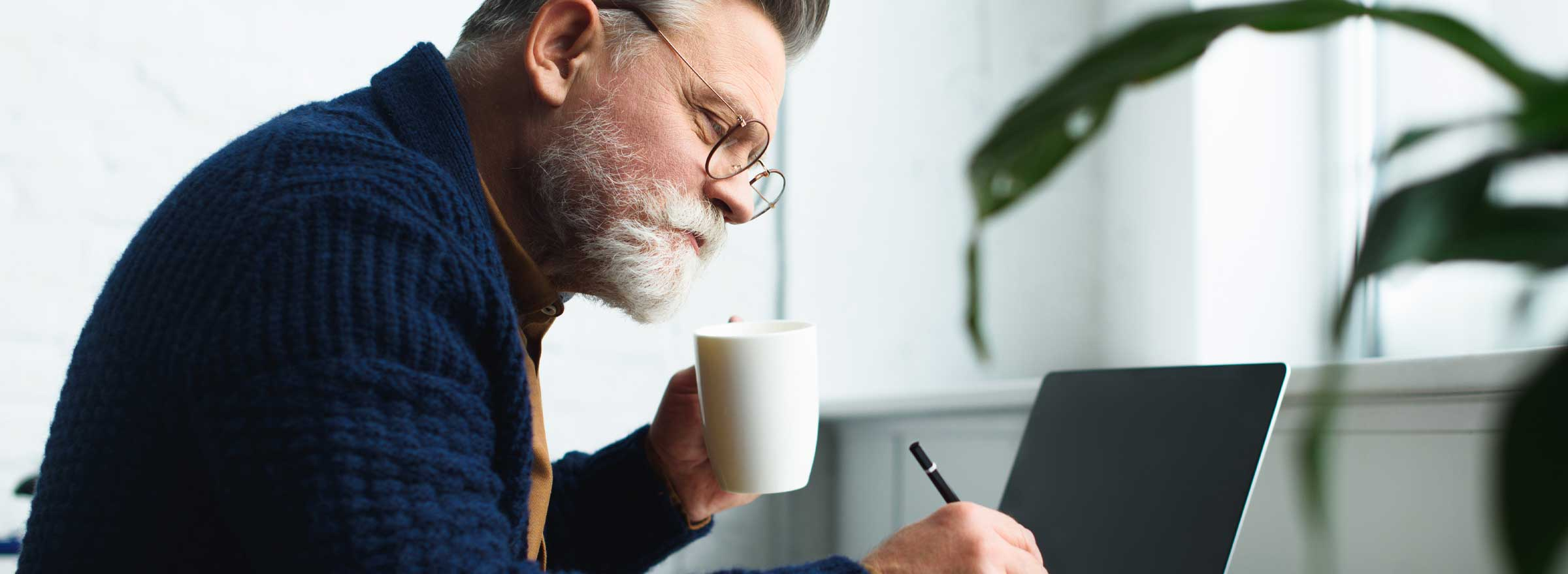 man sitting at a computer, holding a mug, and writing with a pencil or stylus