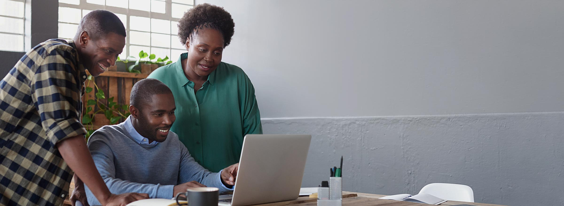 three African American people looking at a laptop together and smiling