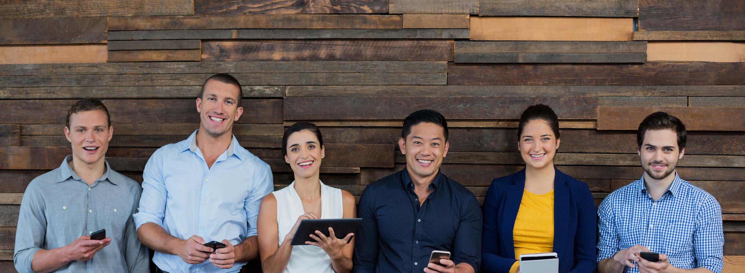 two women and four men standing against a wooden wall, holding cellphones or tablets, and smiling