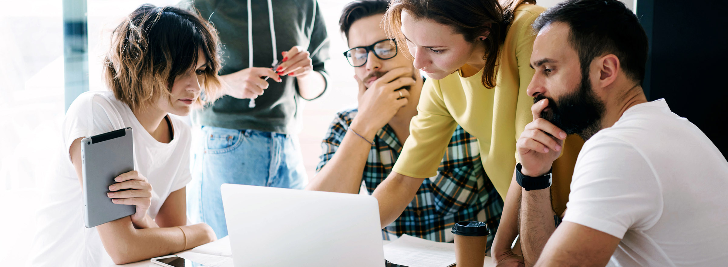 group of people brainstorming around a laptop