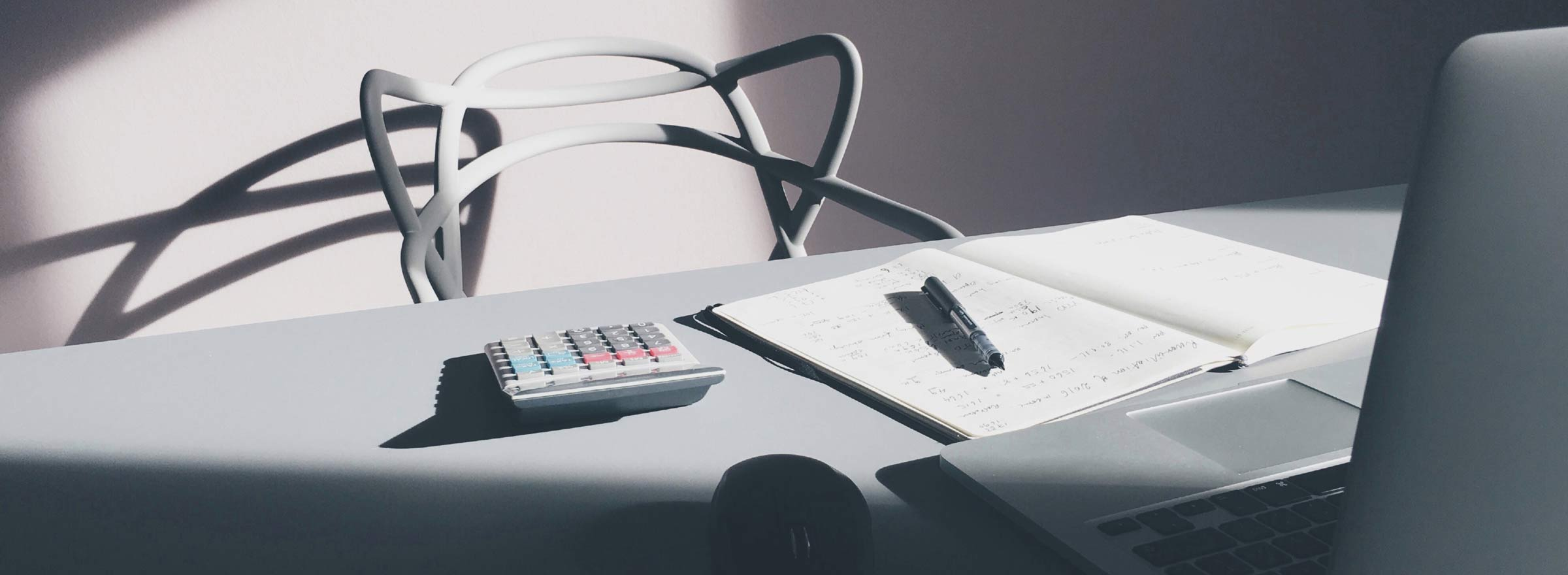 nonprofit accounting tools: a laptop, an open notebook, a pen, and a calculator on a desk in front of a curved chair