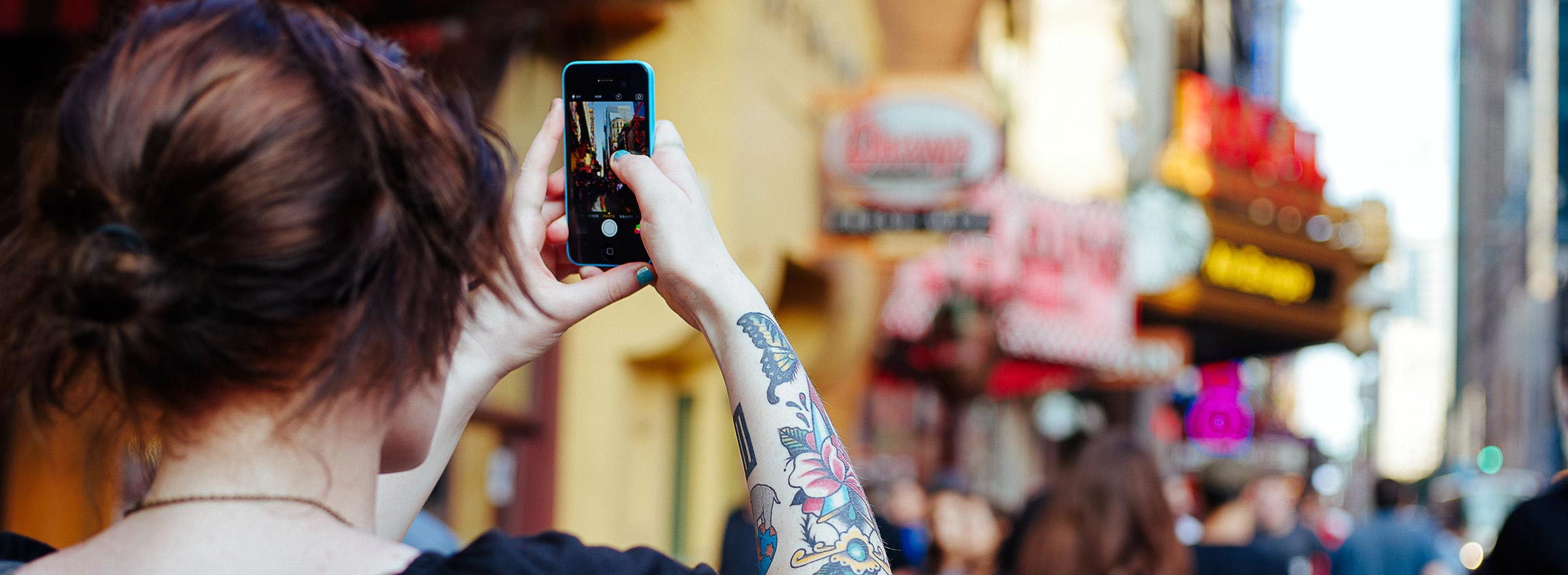 woman with a tattooed arm taking a picture with her cellphone