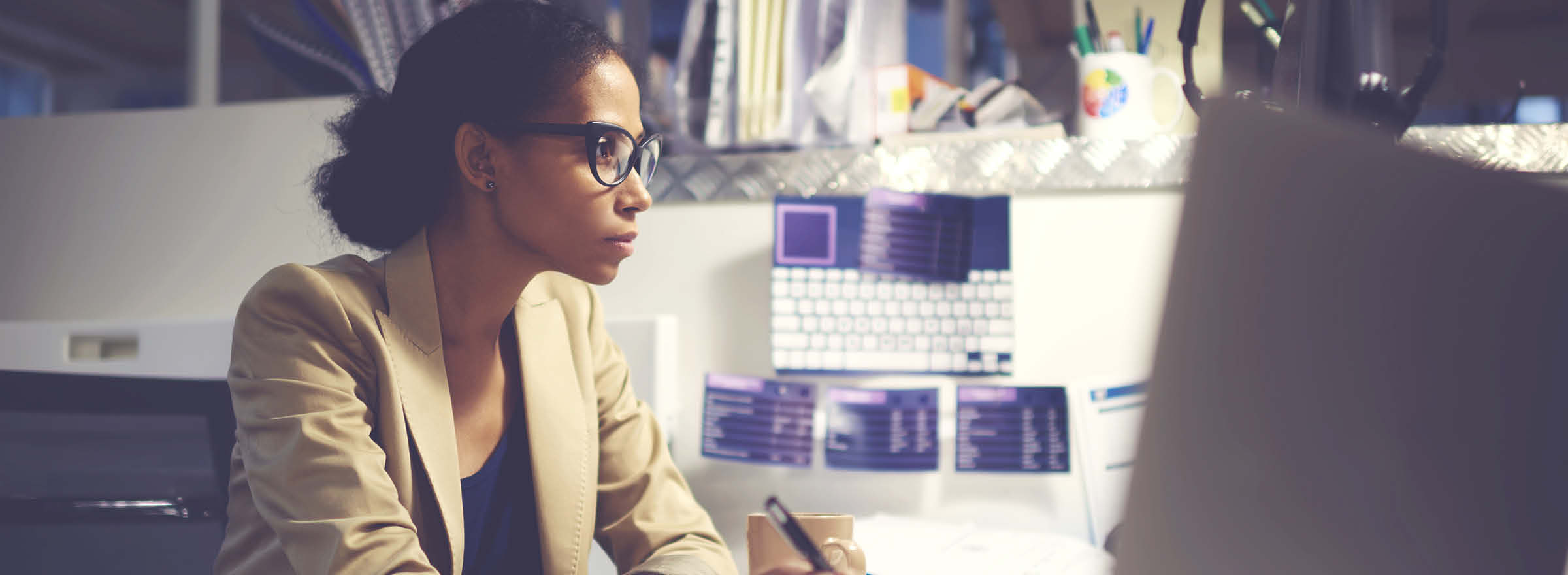An African-American woman dressed in a blazer looking intently at a computer monitor