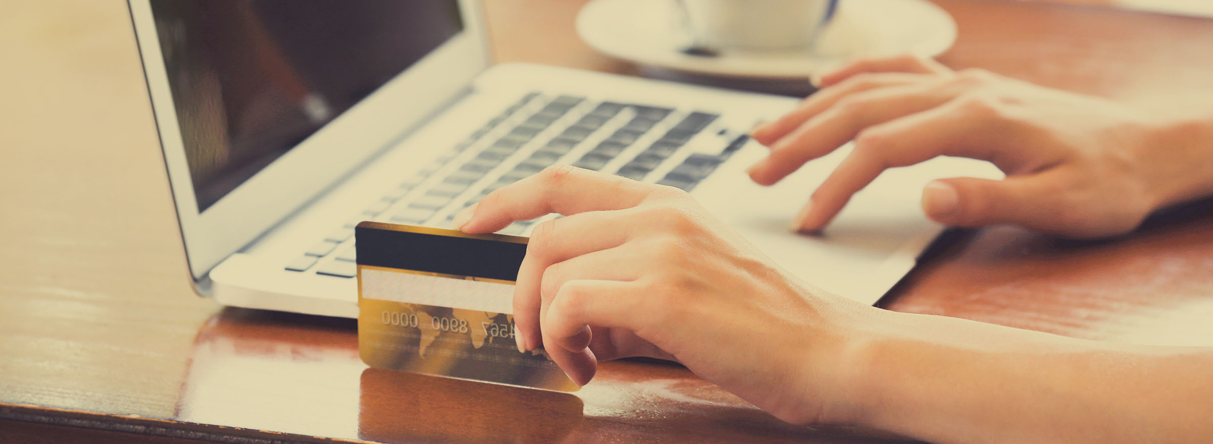 person holding a credit card in left hand and typing on laptop with right hand