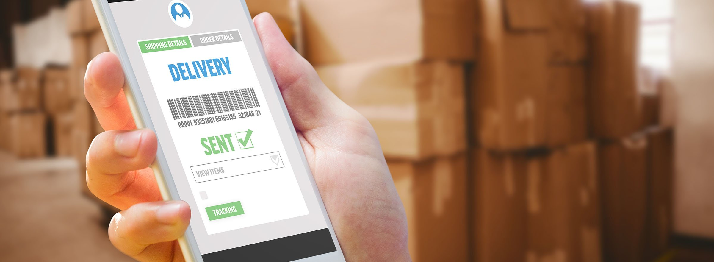 person viewing shipping status on smartphone with boxes stacked in background