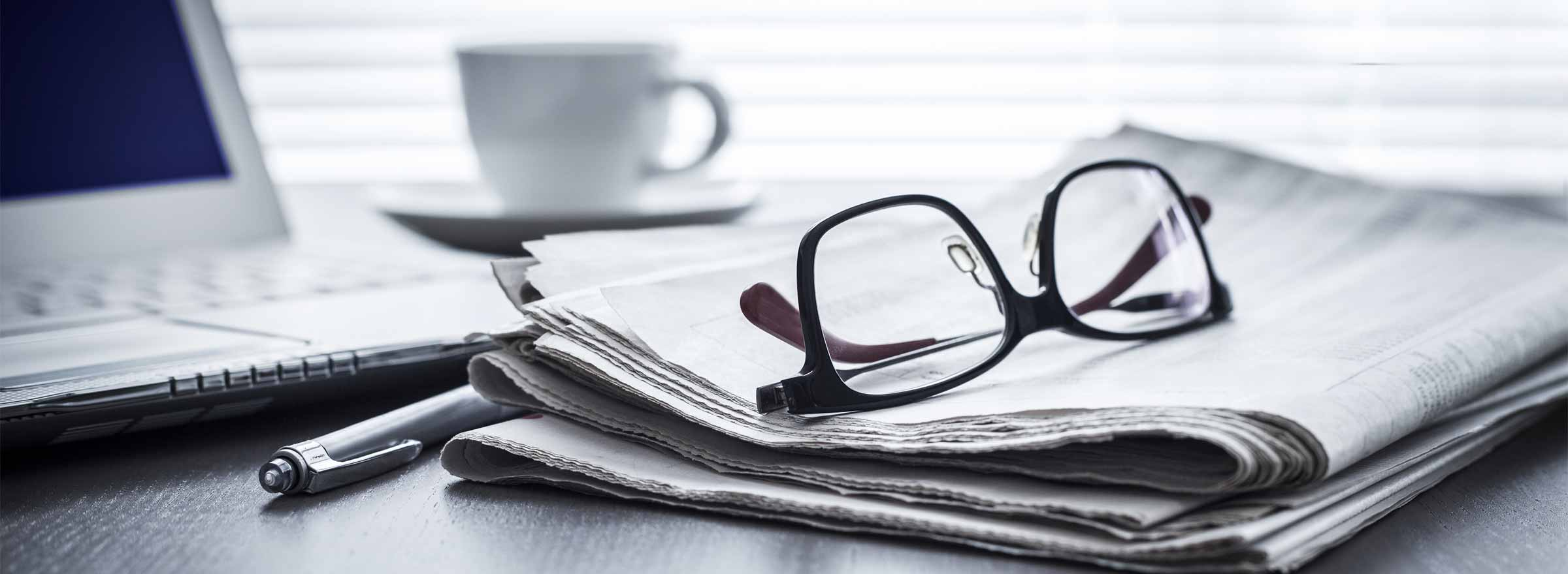 eyeglasses resting on a newspaper in front of a laptop