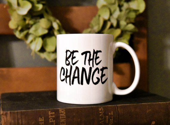white mug with black lettering saying be the change